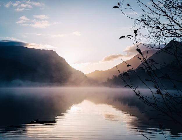 Bella vista su un lago circondato da montagne con un sole splendente sullo sfondo Foto Gratuite