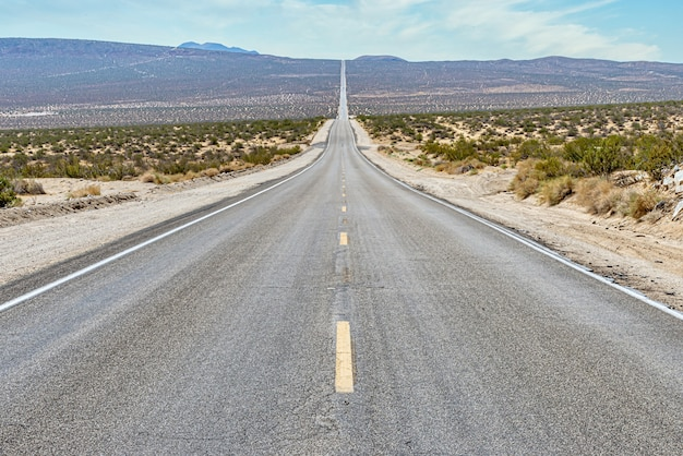 Beautiful view of a long straight concrete road in between the desert field Free Photo