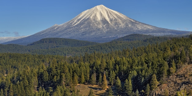 Beautiful view of mount mcloughlin covered in snow over the tree covered hills captured in oregon Free Photo
