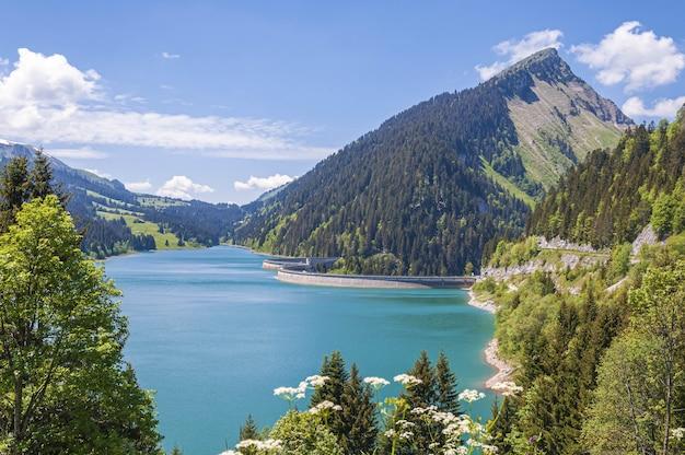 Прекрасный вид на озеро в окружении гор в озере лонгрин и плотине в швейцарии Бесплатные Фотографии