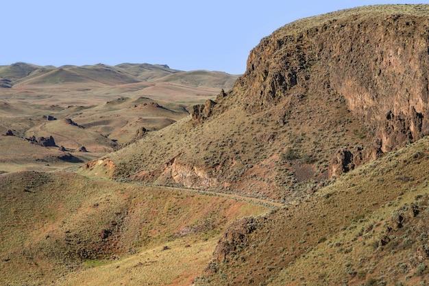 Прекрасный вид на тропу на склоне горы с холмами и голубое небо в фоновом режиме Бесплатные Фотографии
