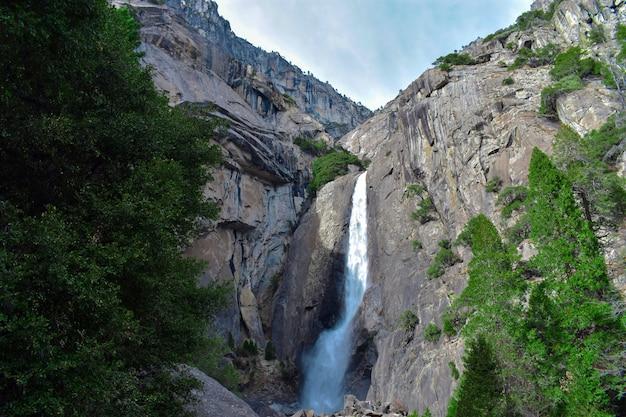 岩から流れる滝と壮大な緑の風景に注ぐ滝の美しい景色 無料写真