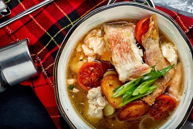 石の背景、上面図に白いプレートで魚のスープの美しいビュー。 Premium写真