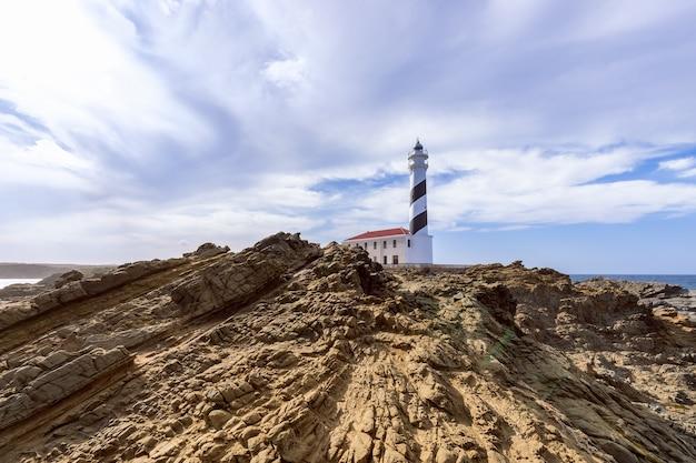Прекрасный вид на маяк под небом с облаками на острове менорка Premium Фотографии