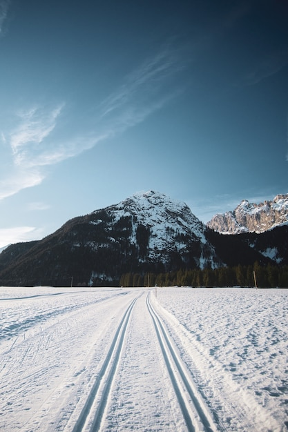 Прекрасный вид на голубое небо с горами и заснеженную дорогу со следами от шин зимой Бесплатные Фотографии