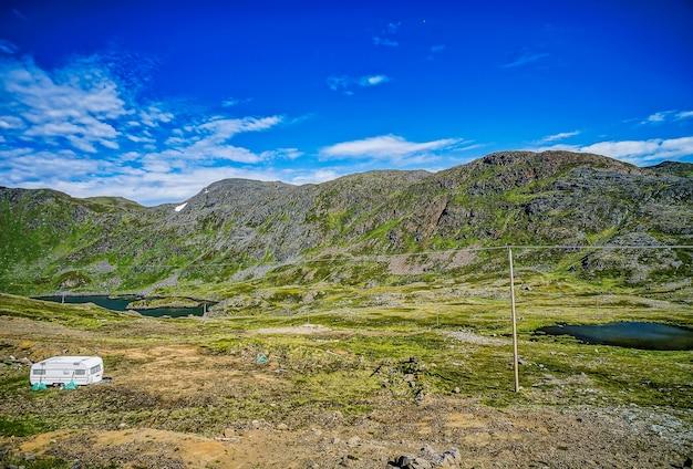 스웨덴의 맑고 푸른 하늘 아래 잔디로 덮인 산과 들판의 아름다운 전망 무료 사진