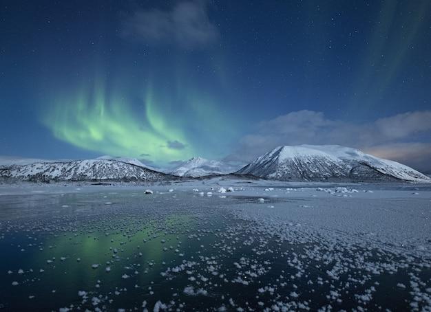 Прекрасный вид на полузамерзшее озеро в окружении заснеженных холмов под северным сиянием Бесплатные Фотографии