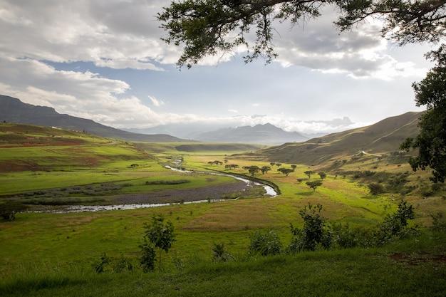 Прекрасный вид на реку, деревья и травы в окружении гор с пасмурным голубым небом. Бесплатные Фотографии