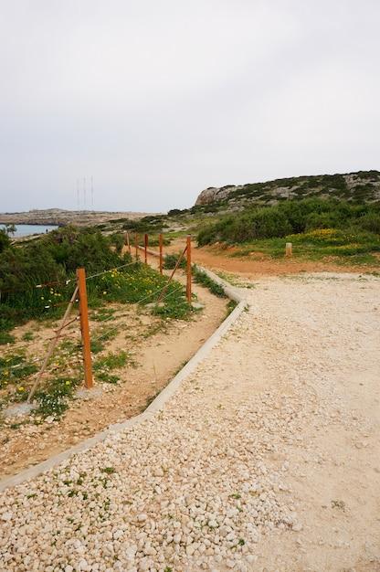 青空の下で草や石に囲まれた海の近くの道路の美しい景色 無料写真