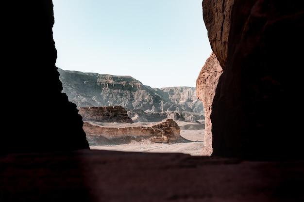 Прекрасный вид на скалы и обрыв в пустыне, снятый из пещеры. Бесплатные Фотографии