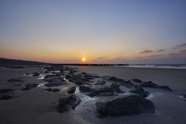 Прекрасный вид на закат с фиолетовыми облаками над пляжем Бесплатные Фотографии