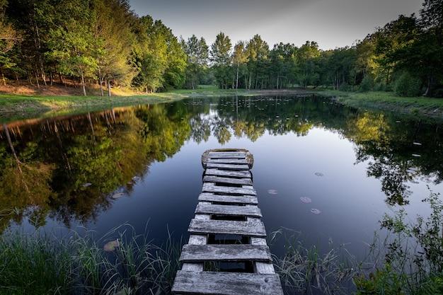 木の遊歩道のある湖に映る紅葉の木々の美しい景色 無料写真