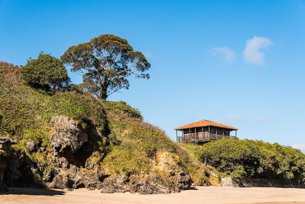 Bella vista di una vecchia casa vicino alla spiaggia circondata da alberi ed erba sotto un cielo blu Foto Gratuite