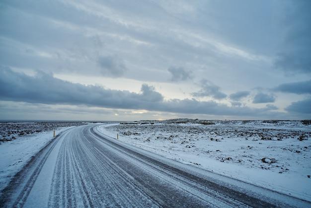 Прекрасный вид на пустую замороженную дорогу со льдом в исландии. океан далеко, облака на небе, противная зимняя погода Бесплатные Фотографии