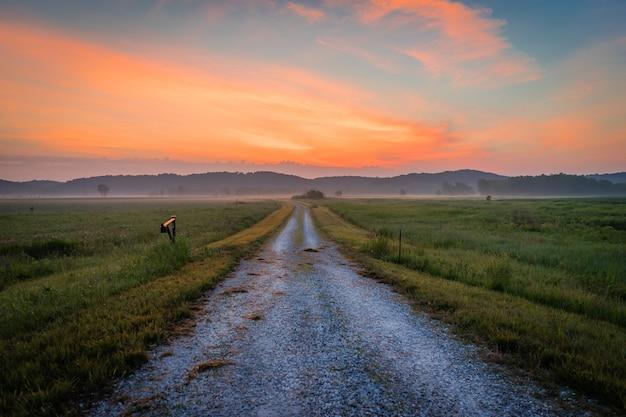 Bella vista di una strada che attraversa i campi sotto il cielo colorato mozzafiato Foto Gratuite