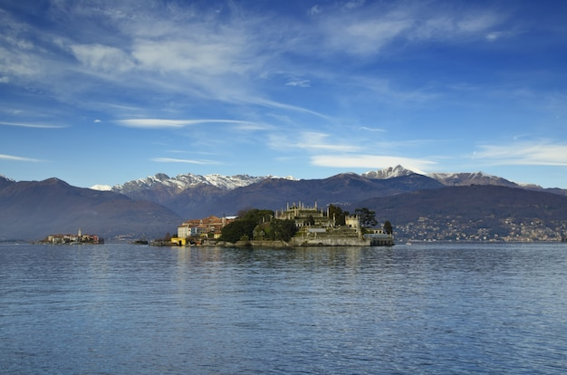 Bella vista di una piccola isola in mezzo al mare vicino alle montagne sotto il cielo blu Foto Gratuite