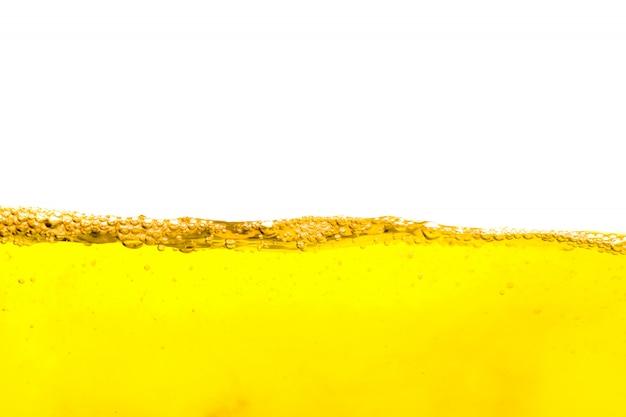 白い背景で隔離の気泡の美しい波、泡、ビールの泡と黄色の夏の飲み物 Premium写真