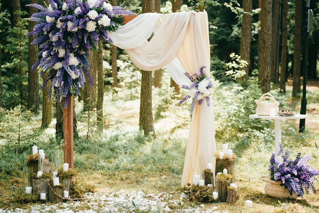 Beautiful wedding arch with blue flowers and decorative elements standing in forest. wedding scenery in rustic style Premium Photo