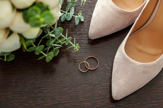 Beautiful wedding bouquet of flowers rings bridal shoes on wood Premium Photo