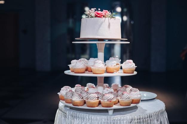 Красивый свадебный торт с цветами на столе Premium Фотографии