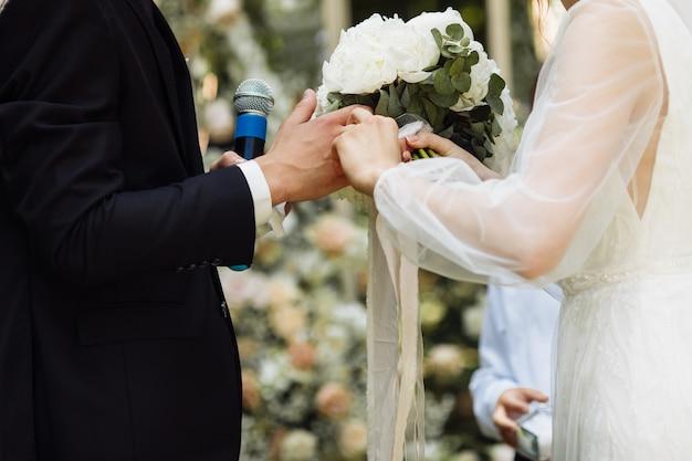 아름다운 결혼식. 네스티와 신랑에 의해 웨딩 아치. 식에서 행복한 신혼 부부. 방문 행사. 아름다운 커플. 프리미엄 사진