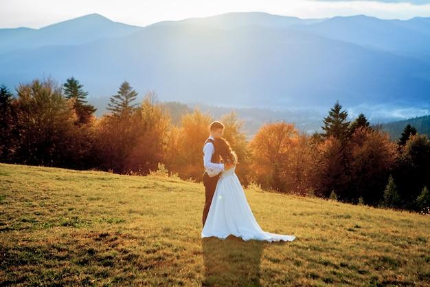 山の恋の美しい結婚式のカップル、新郎新婦。美しいスーツの新郎と白い豪華なドレスの花嫁。結婚式のカップルが歩いています。 Premium写真