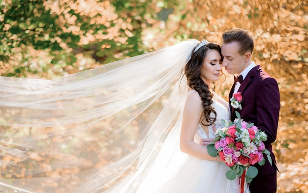 Beautiful wedding couple in the forest with yellowed trees almost kissing, marriage concept, wedding couple in autumn forest Free Photo