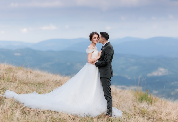 Beautiful wedding couple is kissing on the top of a mountain in the autumn warm day Free Photo