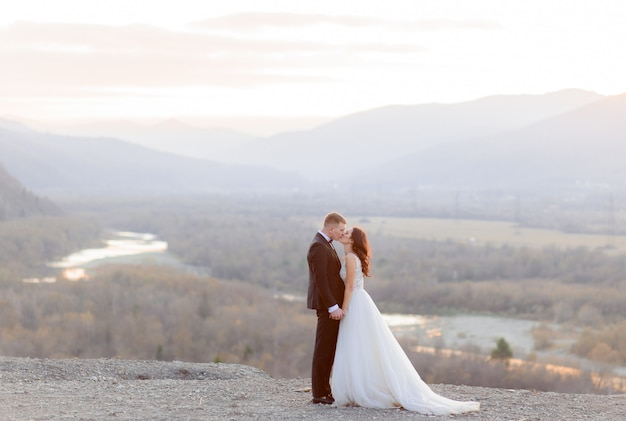 Beautiful wedding couple is kisssing on the hill with a view of a picturesque landscape in the dusk Free Photo