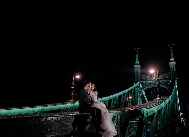 Beautiful wedding couple is sitting on the illuminated bridge on the dark night and kissing Free Photo
