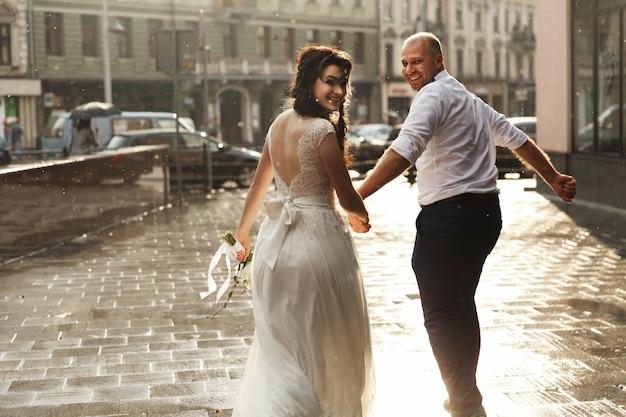 Beautiful wedding couple looks happy walking around the city in the rain Premium Photo