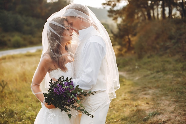 Beautiful wedding couple in a summer field Free Photo