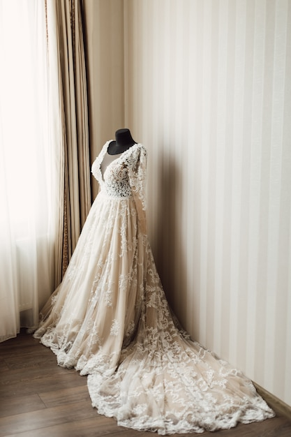 Beautiful wedding dress with plume is dressed on a mannequin Free Photo
