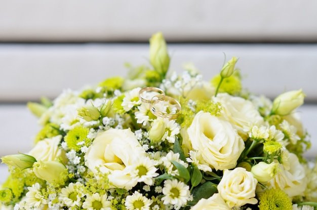 Beautiful wedding flowers bouquet with two wedding rings Premium Photo