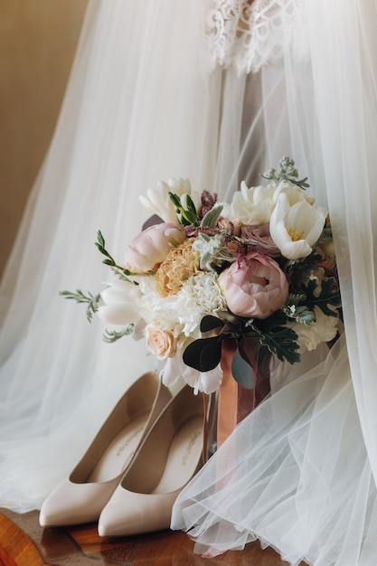 Beautiful wedding shoes, dress and flower bouquet Free Photo