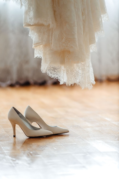 Beautiful wedding shoes and dress on a wooden brown floor Premium Photo