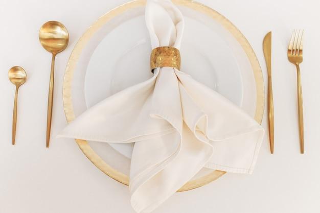 아름 다운 결혼식 식기 흰색 테이블에 놓여 있습니다. 금 숟가락과 포크. 프리미엄 사진