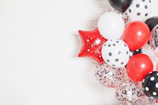 빨간색, 흰색 및 검은 색 풍선과 함께 아름 다운 흰색 벽돌 벽 배경. 행복과 기쁨의 개념. 공간 복사 프리미엄 사진