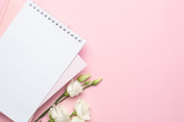 Beautiful white flower and notebook on pink Premium Photo
