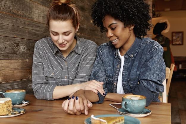 トレンディなデニムジャケットで彼女のファッショナブルな黒のガールフレンドに話している髪のお団子と美しい白いレズビアン 無料写真