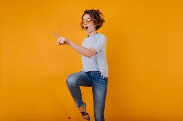 노란색 공간에 점프 유행 데님 바지에 아름 다운 백인 여자 무료 사진