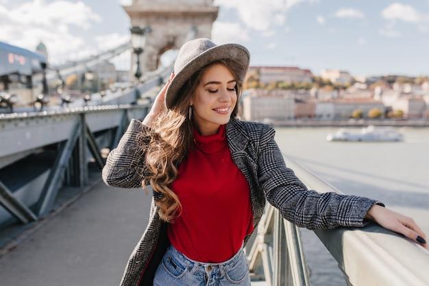 Beautiful white woman wears soft red sweater enjoying city views in travel Free Photo