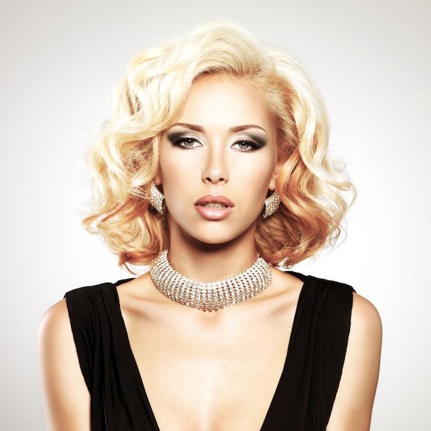 Красивая белая женщина с кудрявой прической и серебряным украшением позирует в студии Бесплатные Фотографии