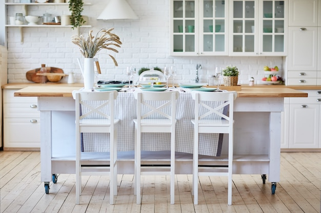 Beautiful white wooden kitchen with island table and chairs. Premium Photo