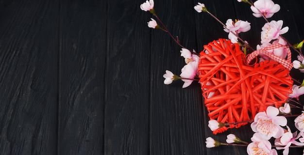 黒い背景にピンクの花と美しい籐の赤い心 Premium写真