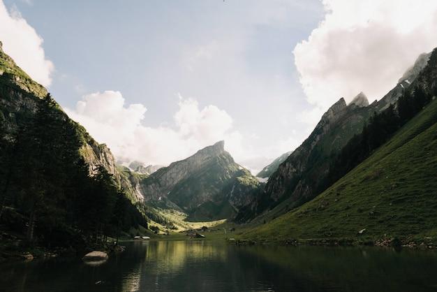 Красивый широкий снимок озера, окруженного зелеными горами Бесплатные Фотографии
