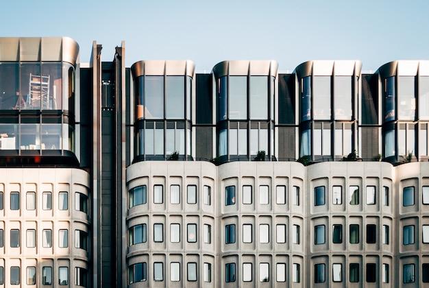 澄んだ青い空の下で大きなガラス窓のあるモダンな白い建築の美しいワイドショット 無料写真