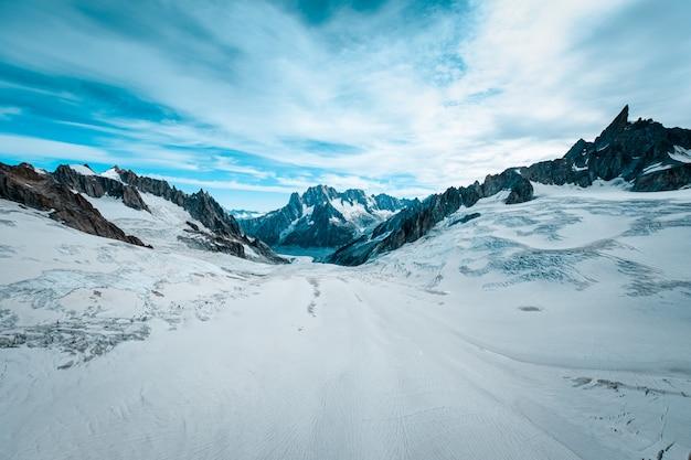 白い雲と青い空の下で雪に覆われたルース氷河の美しいワイドショット 無料写真