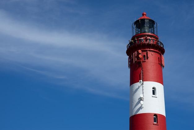 해변에서 맑은 날에 빨간색과 흰색 등대 타워의 상단의 아름다운 넓은 샷 무료 사진