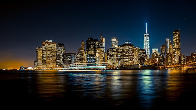 Beautiful wide shot of an urban city at night with a boat Free Photo